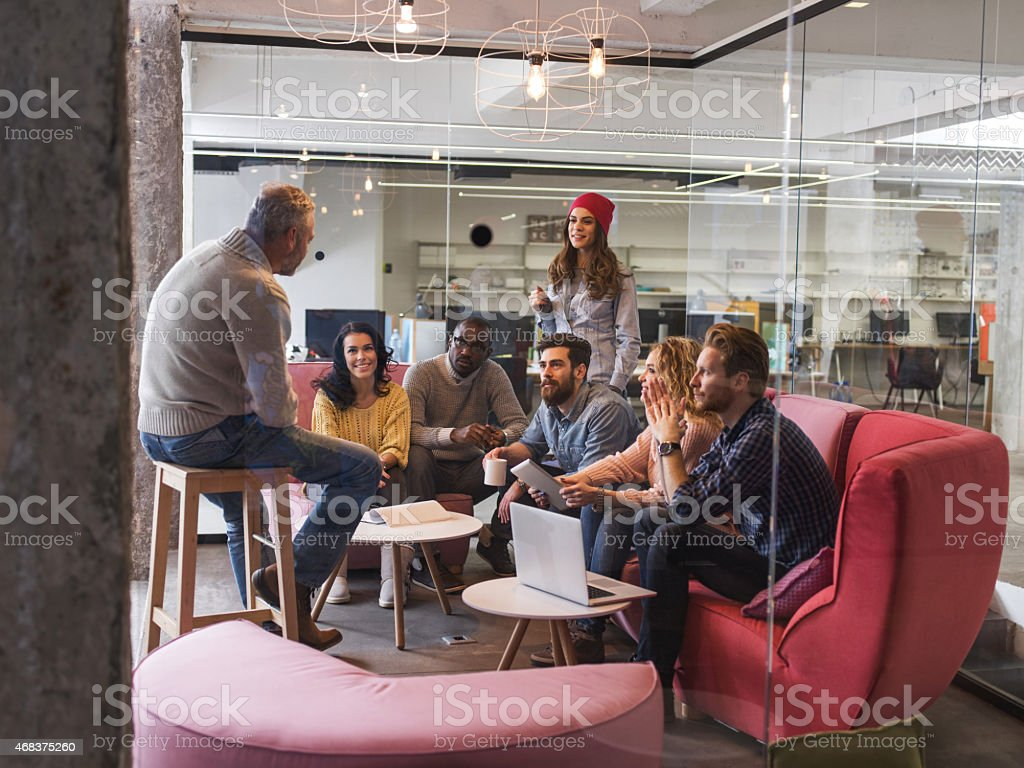 Start up team having a meeting. View is through glass. stock photo