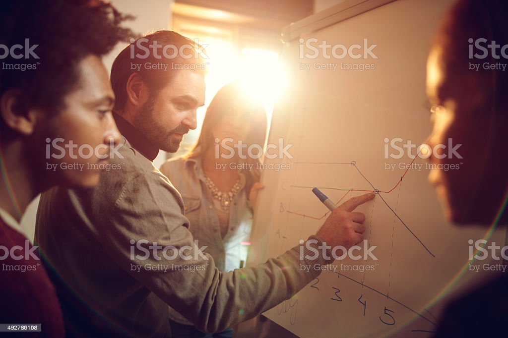 Start up team working on a business chart together. stock photo