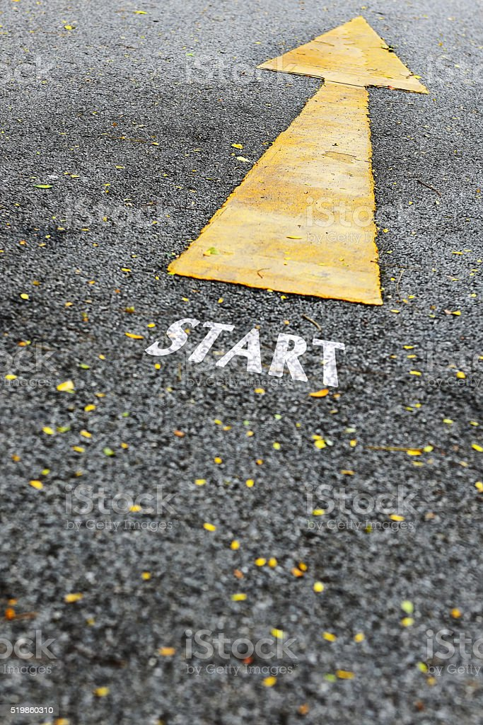 Start word and single yellow arrow sign marking on road stock photo