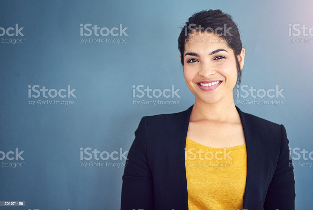 Cropped studio portrait of a young businesswoman standing against a...