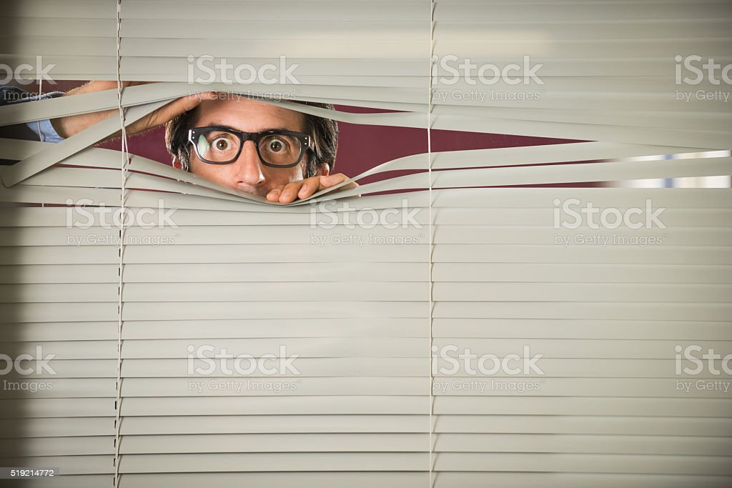 Startled Nerd staring Through Venetian Blinds stock photo