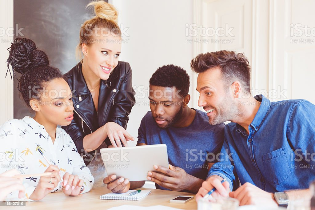 Start-up agency, multi ethnic team using digital tablet together stock photo