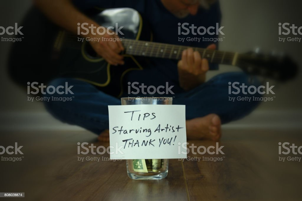 Starving artist guitarist street performer with tip cup jar stock photo