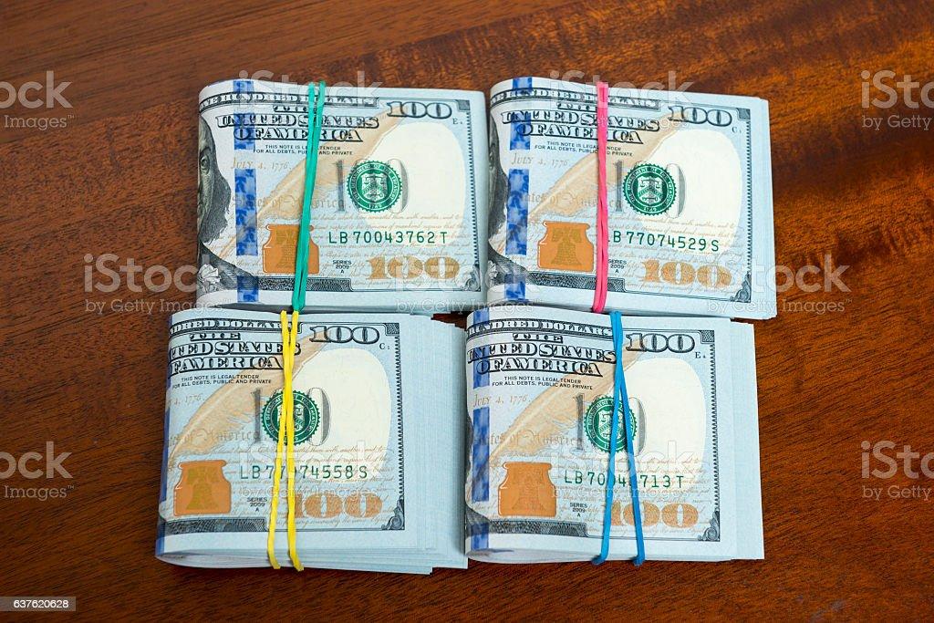 Stashes of hundred dollar bills on wooden table stock photo