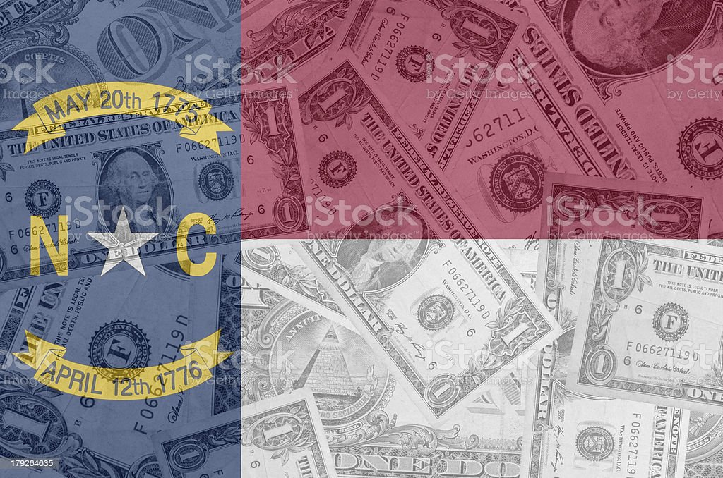 US state of north carolina flag with transparent dollar banknotes stock photo