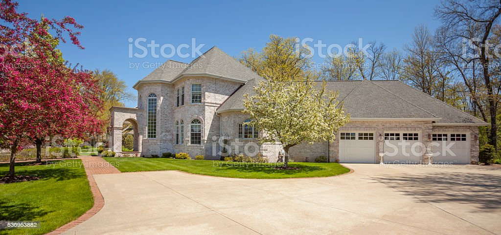 Stately mansion home with blossoming trees, three stall garage. stock photo