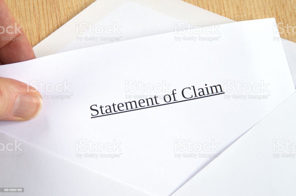 Statement of Claim printed on white paper and envelope, hand holding it, wooden background stock photo