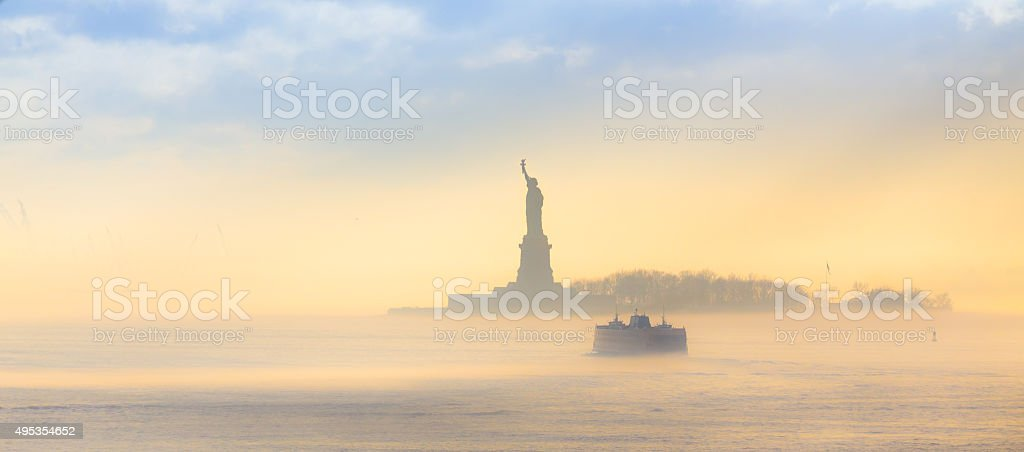 Staten Island Ferry cruises past the Statue of Liberty. stock photo