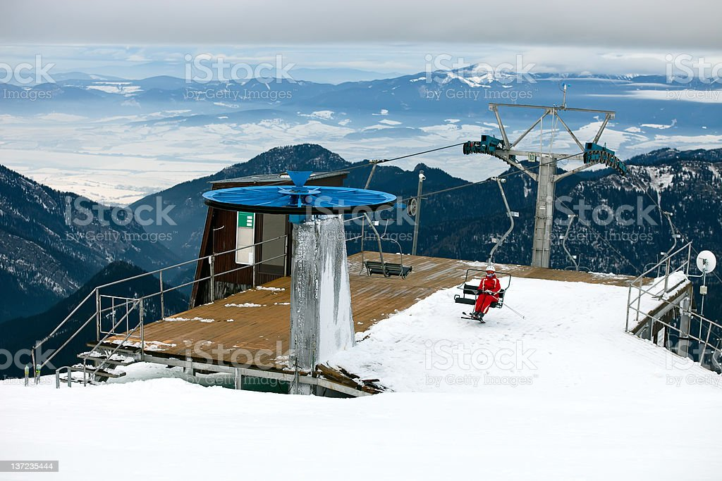 Station of the ski lift, female skier on chairlift. royalty-free stock photo