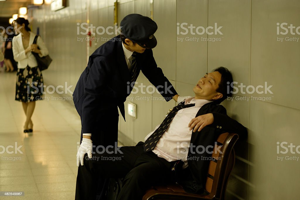 Station staff looking after drunken businessman stock photo