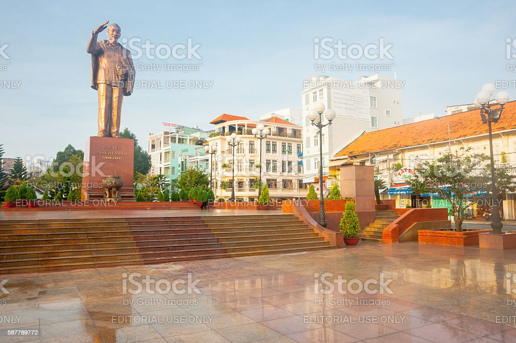 Statue Ho Chi Minh standing saluting mounted on high plinth stock photo