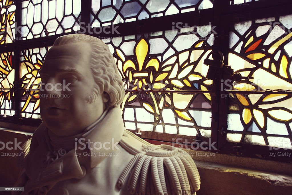 Statue in front of stained glass windows, France royalty-free stock photo