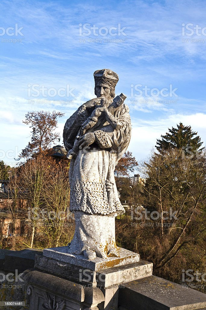 statue of a bishop with cross stock photo