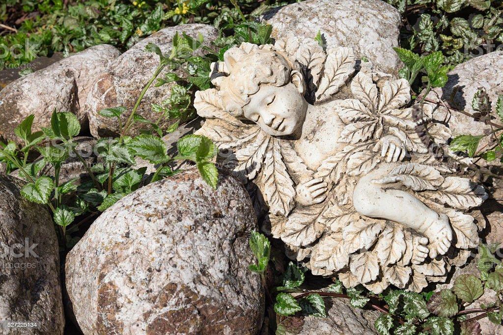 Statue of an elf  sleeping in the garden stock photo