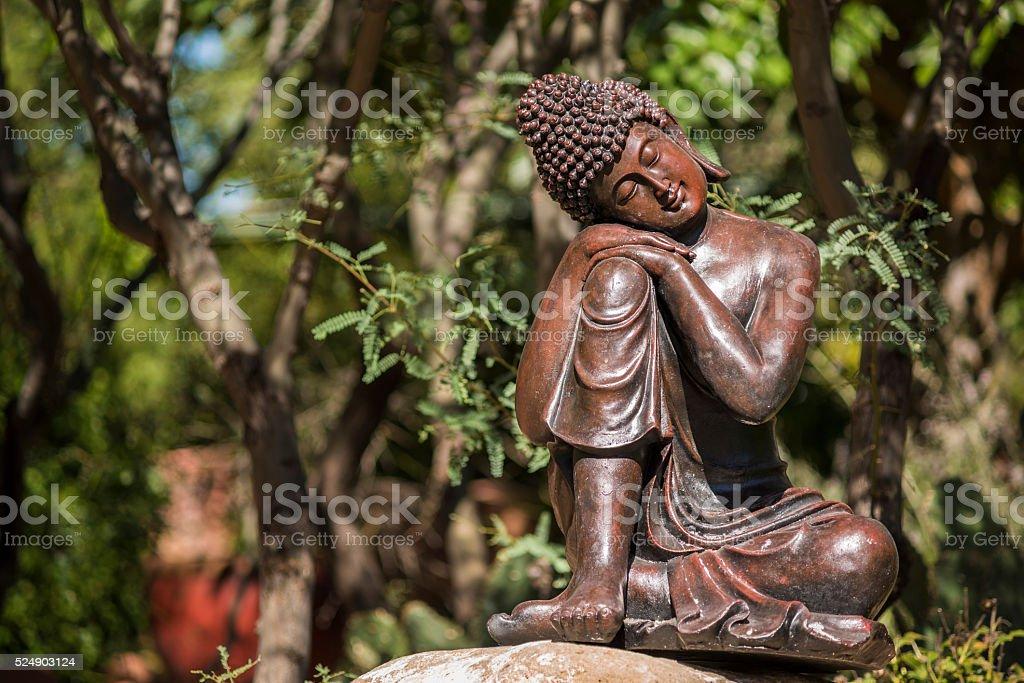 Statue of bronze buddha sleeping in a garden stock photo