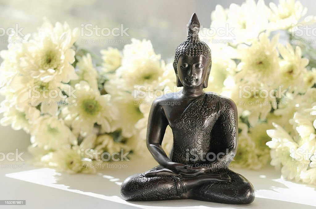 statue of Buddha with white flowers royalty-free stock photo