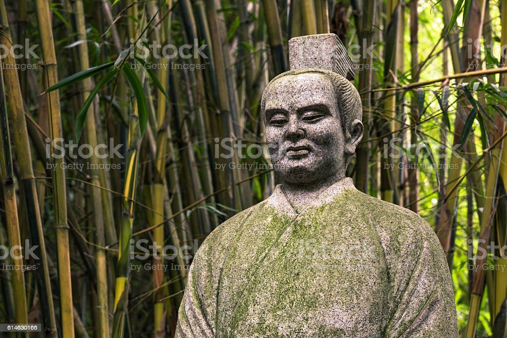 statue of chinese ancient man with bamboo background stock photo