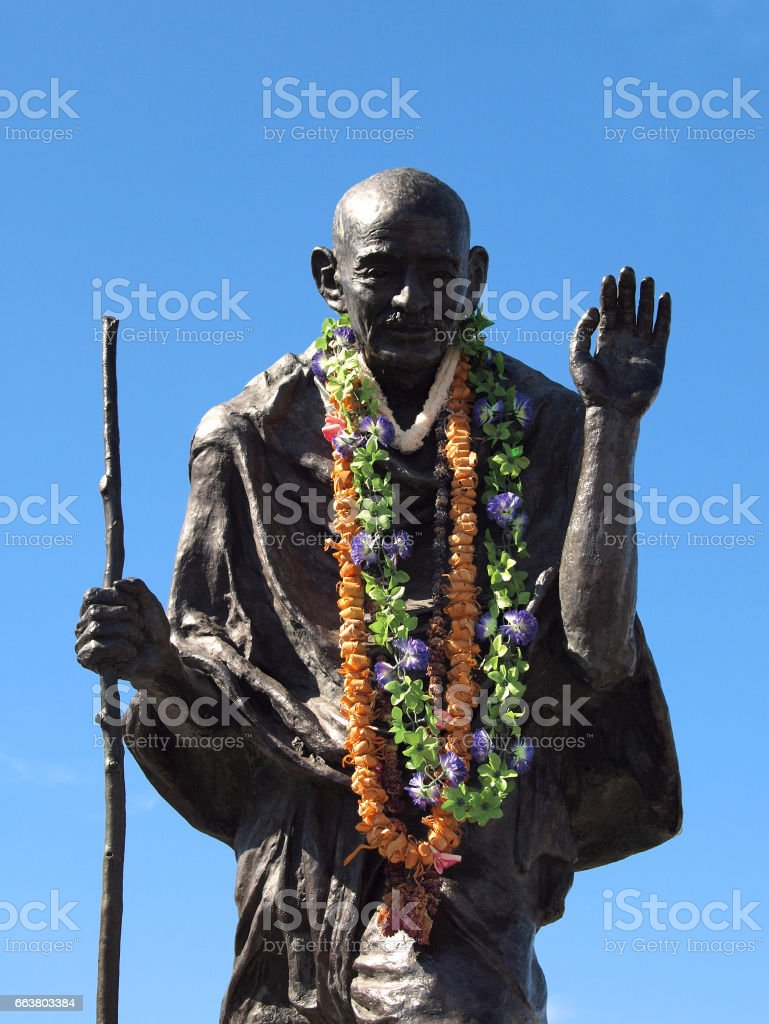 Statue of Ghandi wearing real leis stock photo