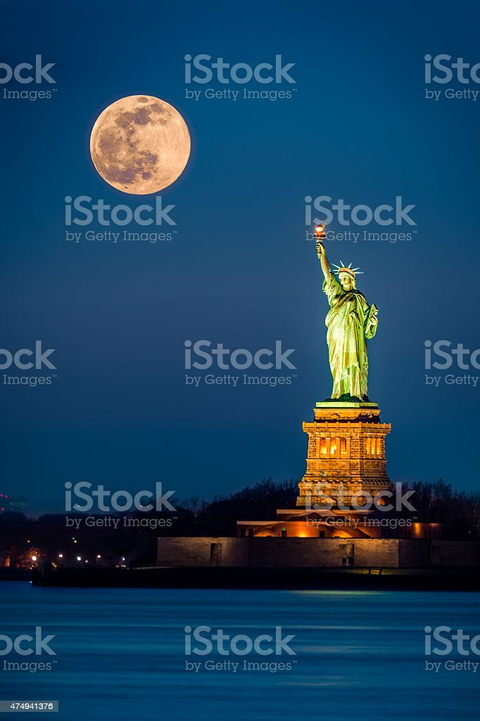 Statue of Liberty and a rising supermoon stock photo