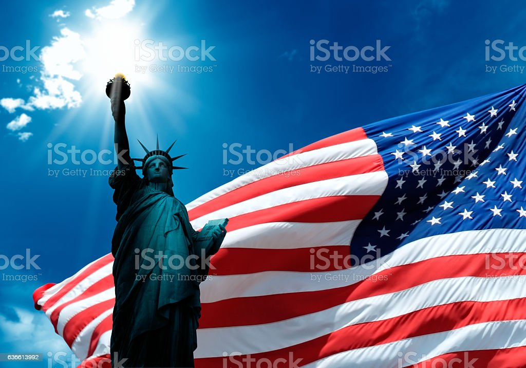 statue of liberty and waving american flag stock photo