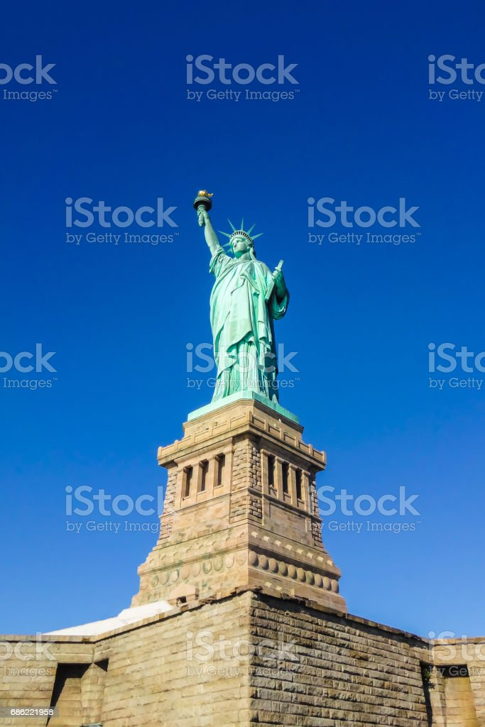 Statue of Liberty at perfect weather conditions blue sky copper torch stock photo