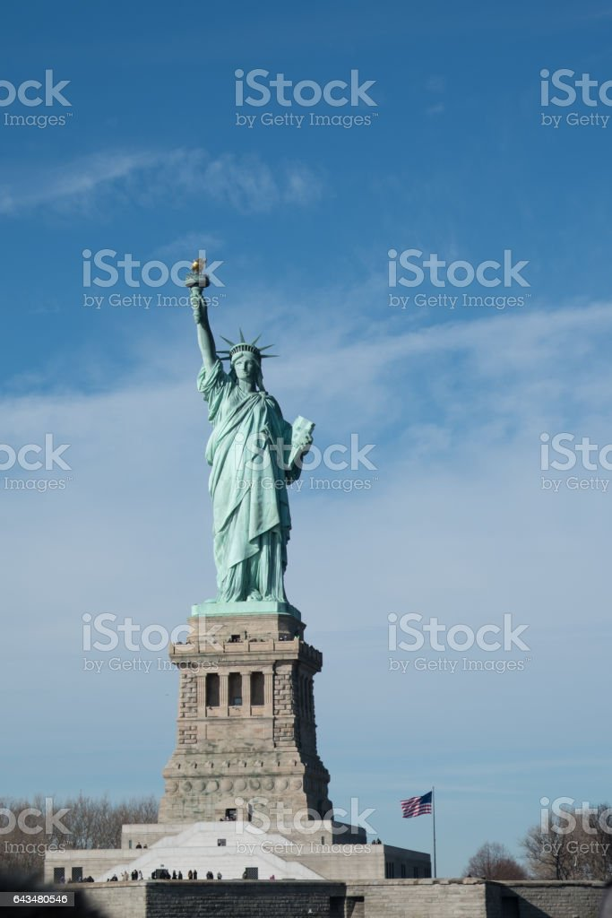 Statue of Liberty on Liberty Island, American Flag on a flagpole waving in background. Statue of Liberty on a bright sunny day with blue sky and scattered clouds, view from a ferry in New York Harbor. stock photo