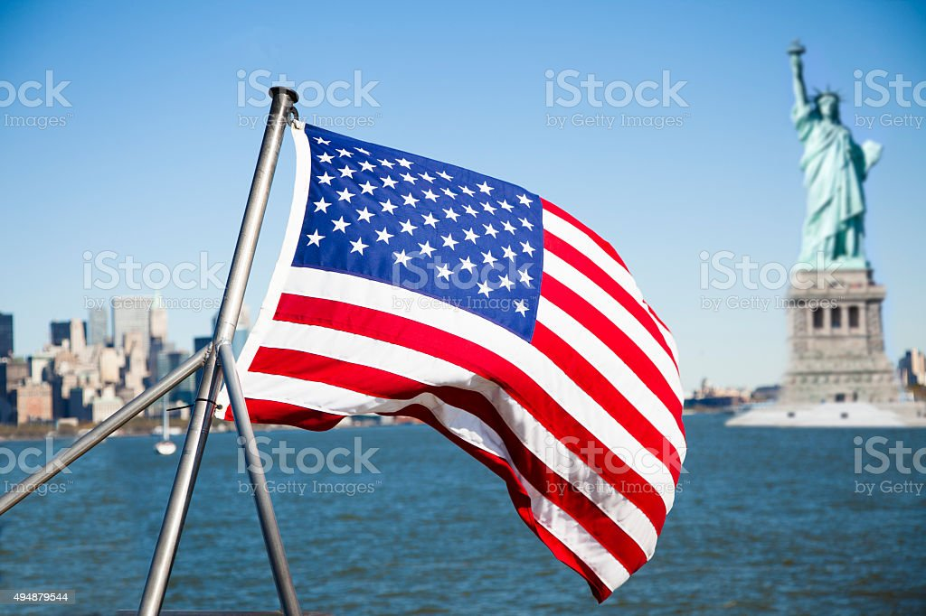 Statue of Liberty with American flag in foreground. stock photo