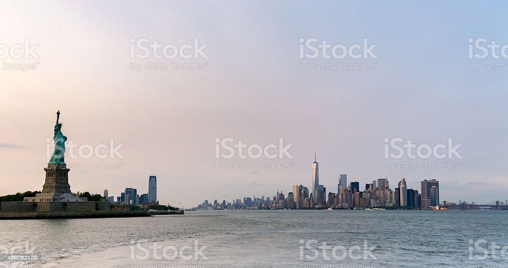 Statue of Liberty with Manhattan at Sunset stock photo