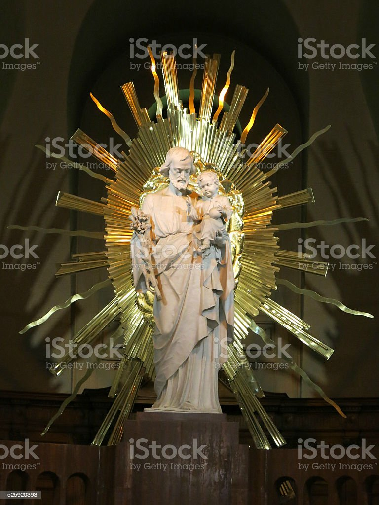 Statue of Saint Joseph holding Baby Jesus with Gold Rays stock photo