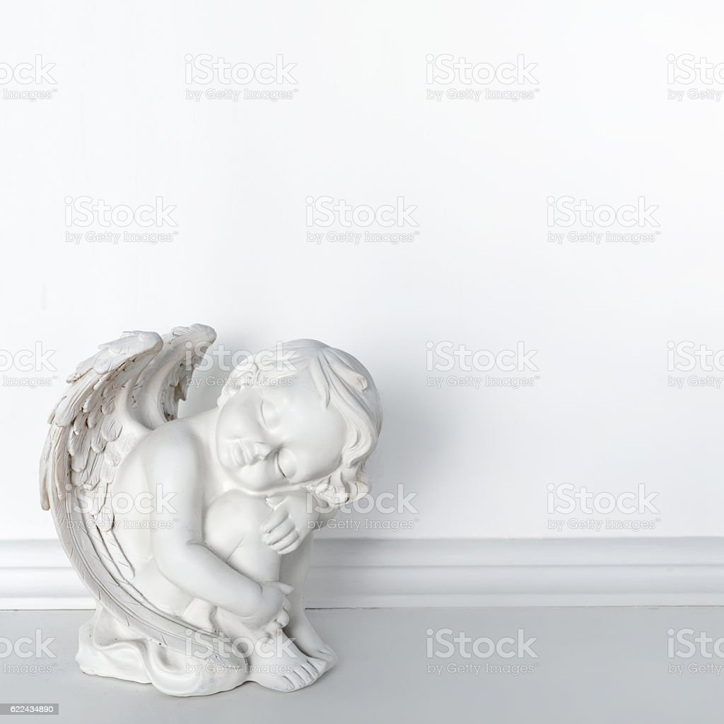 Statue of Sleeping Cupid on white background with copy space stock photo