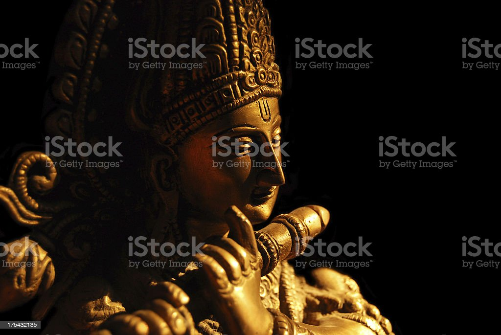 Statue of the Hindu God Krishna playing a flute stock photo