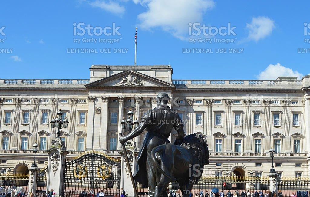 Estatua con el Palacio de Buckingham de fondo foto de stock libre de derechos