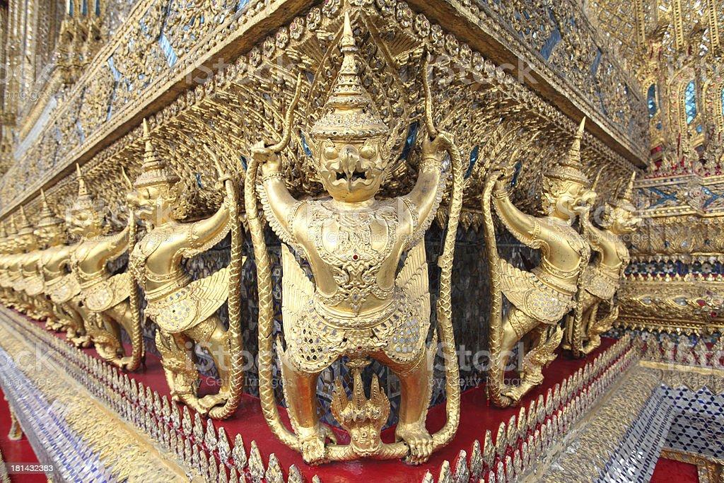 Statues of Garuda battling naga serpent on the wall royalty-free stock photo