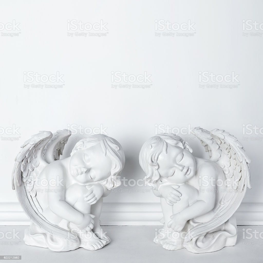 Statues of Sleeping Cupids on white background with copy space stock photo