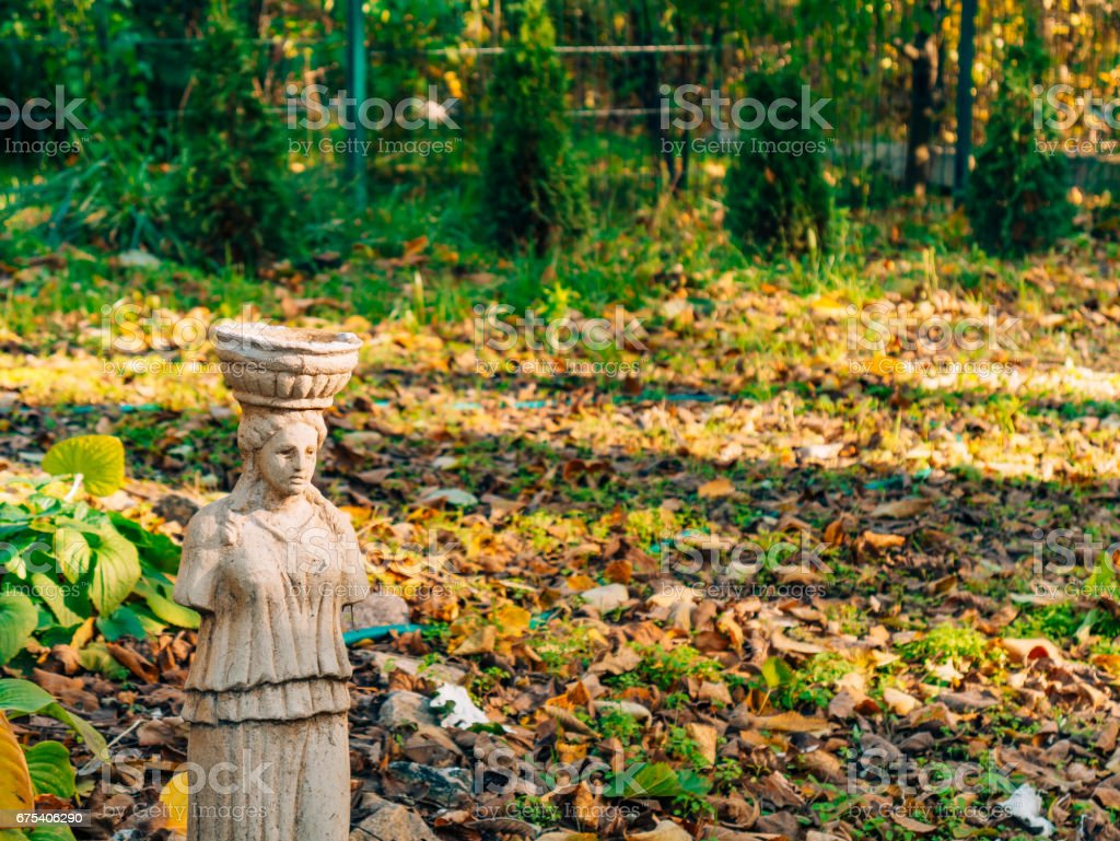 Statues without hands beside a wooden bench stock photo