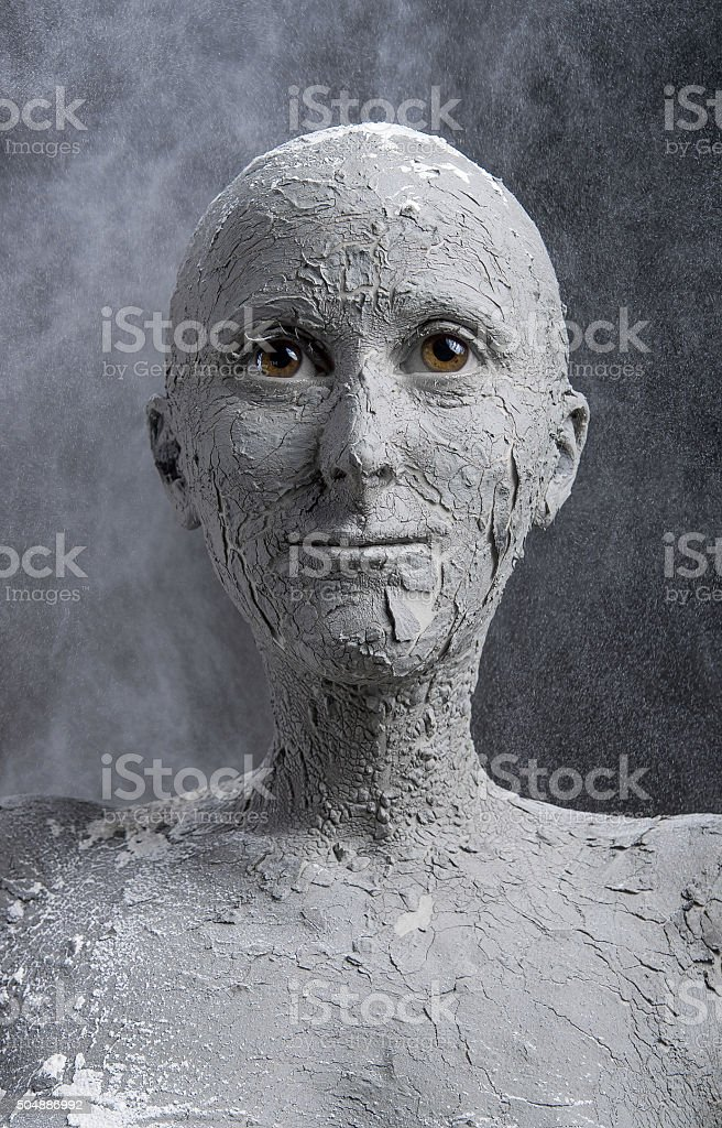 Statuesque woman in clay. Spa treatment stock photo