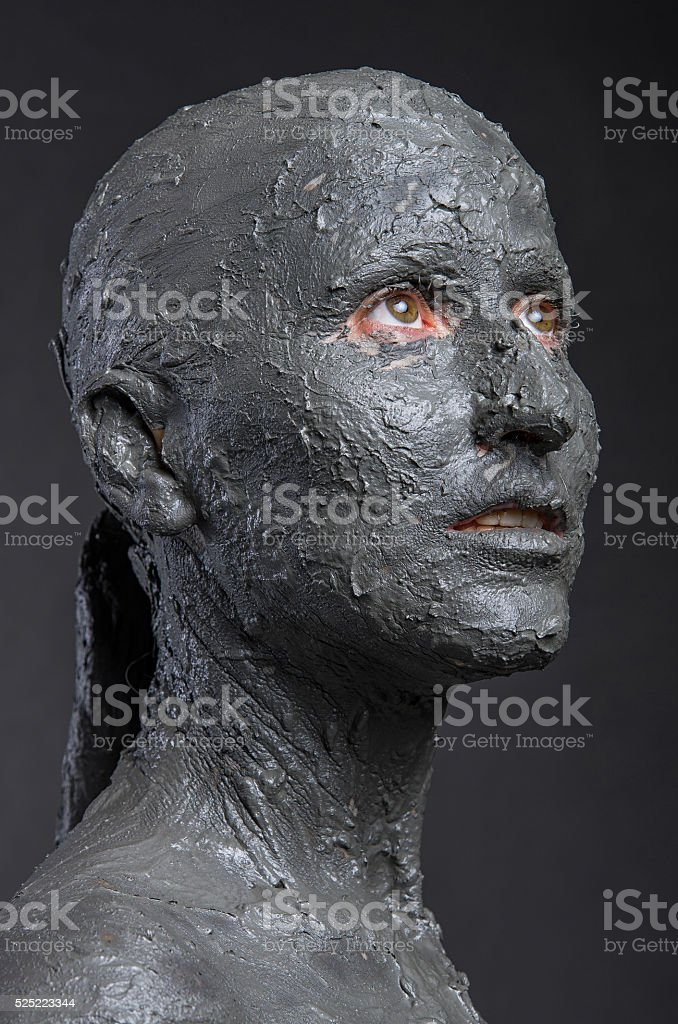 Statuesque woman in wet clay. Spa treatment. stock photo