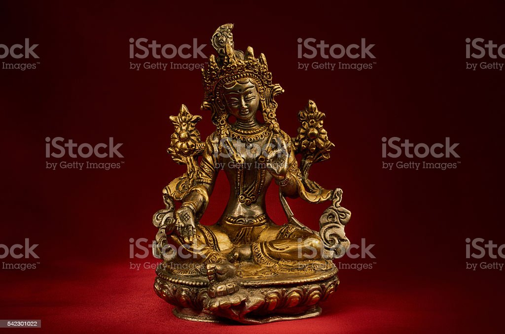 Statuette of Green Tara on a red background. stock photo