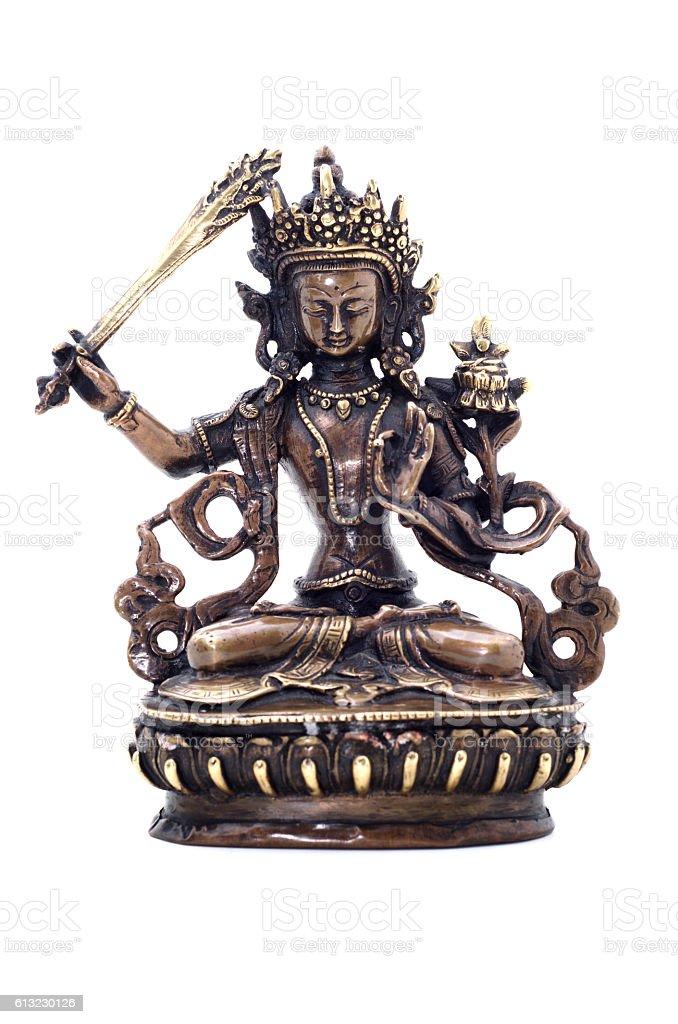 Statuette of Manjushri brandishing sword of wisdom. stock photo
