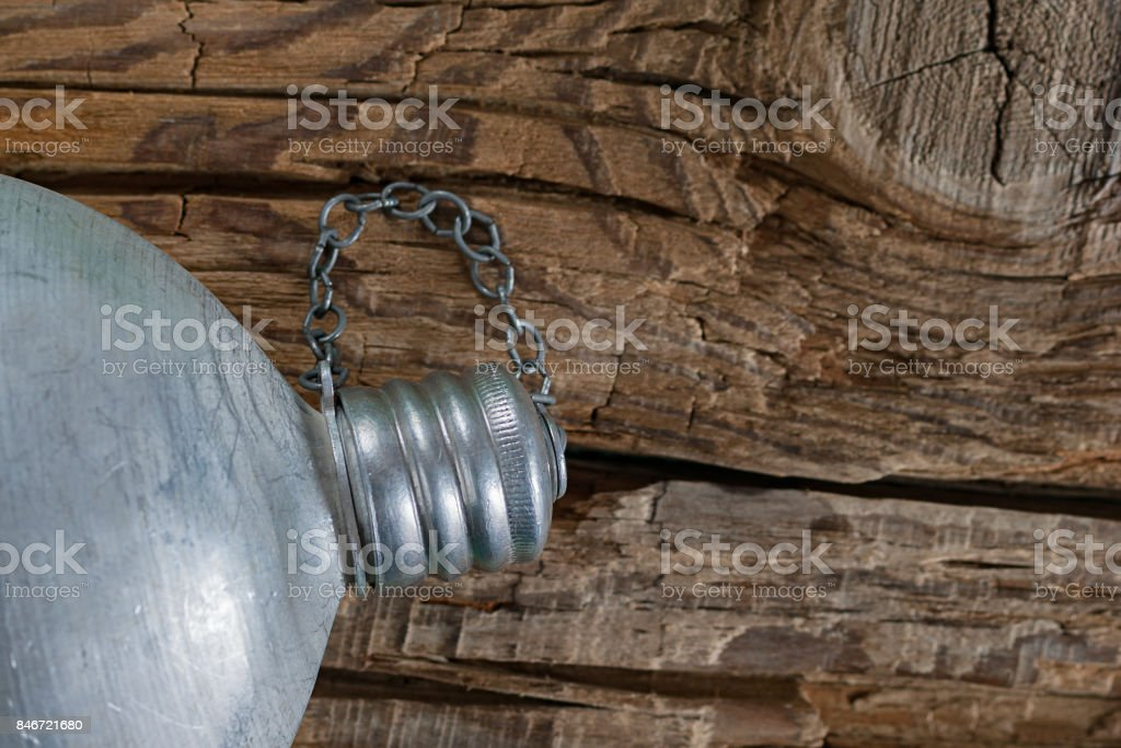 Staying hydrated concept. Full vintage military aluminum canteen, water flask with cap screwed on coarse weathered wood background. stock photo