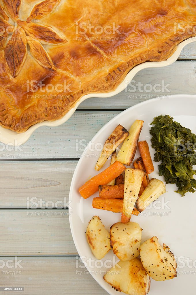 Steak and Ale Pie with plate of vegetables on table stock photo