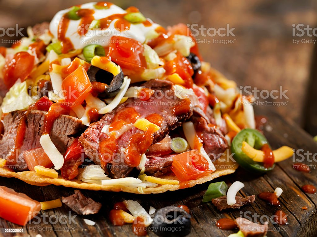 Steak and Cheese Tostada with Hot Sauce stock photo