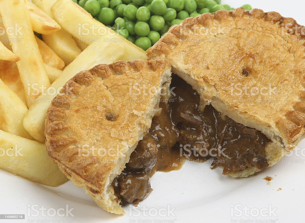 Steak and kidney pie with chips and peas stock photo