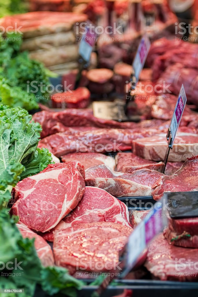 Steak and other meats at butchers counter. stock photo