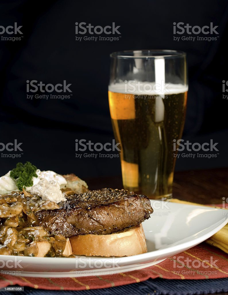 A steak and potato roast meal served with a lager stock photo