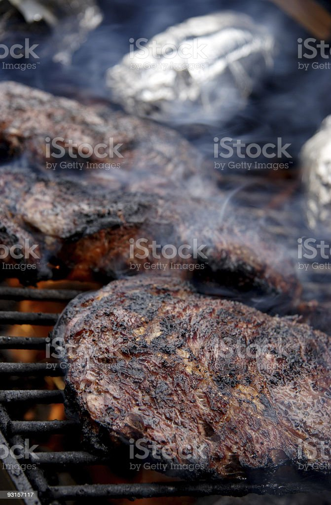 steak and potatoes grilling stock photo