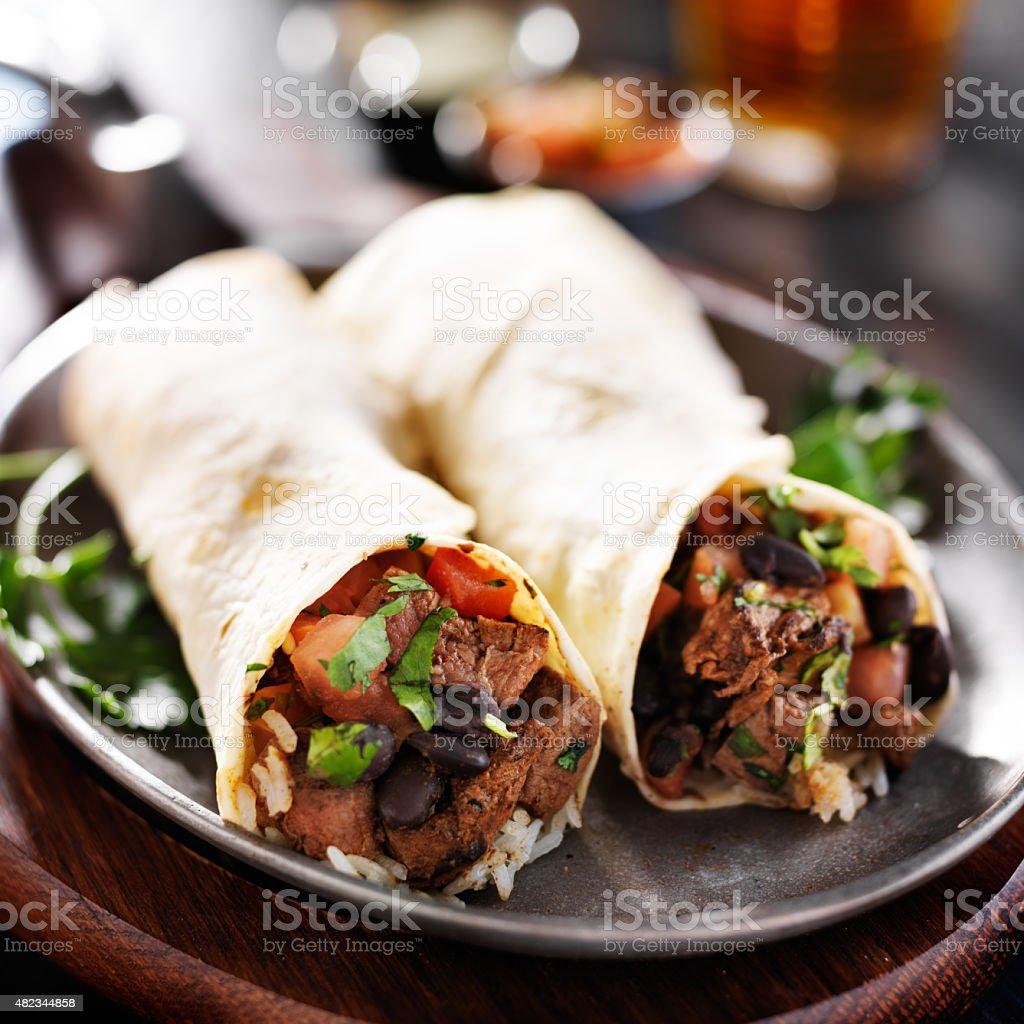 steak and rice mexican burritos stock photo