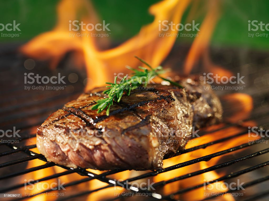 steak barbecue with flames stock photo
