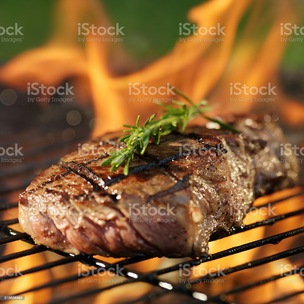 steak cooking over flaming grill stock photo