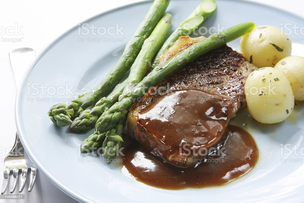 Steak dinner with asparagus and potatoes on a white plate royalty-free stock photo